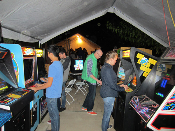 Gamers enjoy the row of arcade cabs outside.  The lighted tent in the background is the crowded trade area
